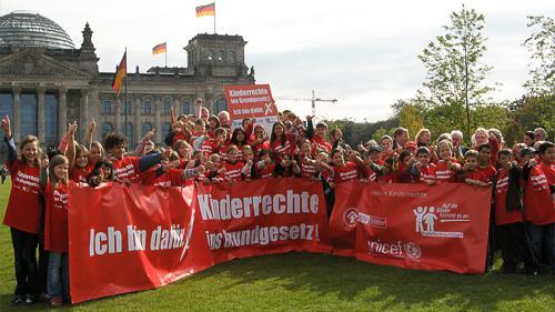 Kinder vom Deutschen Kinderhilfswerk halten PVC Banner vor dem deutschen Reichstag